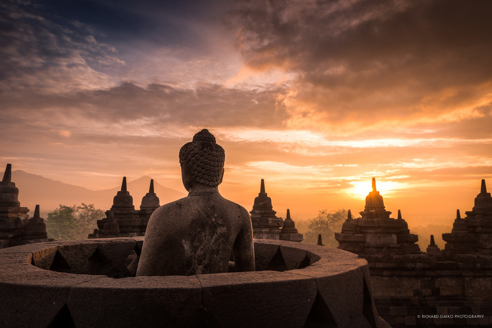 Borobudur sunrise. Statue of Buddha is overlooking the distant Merapi volcano.
