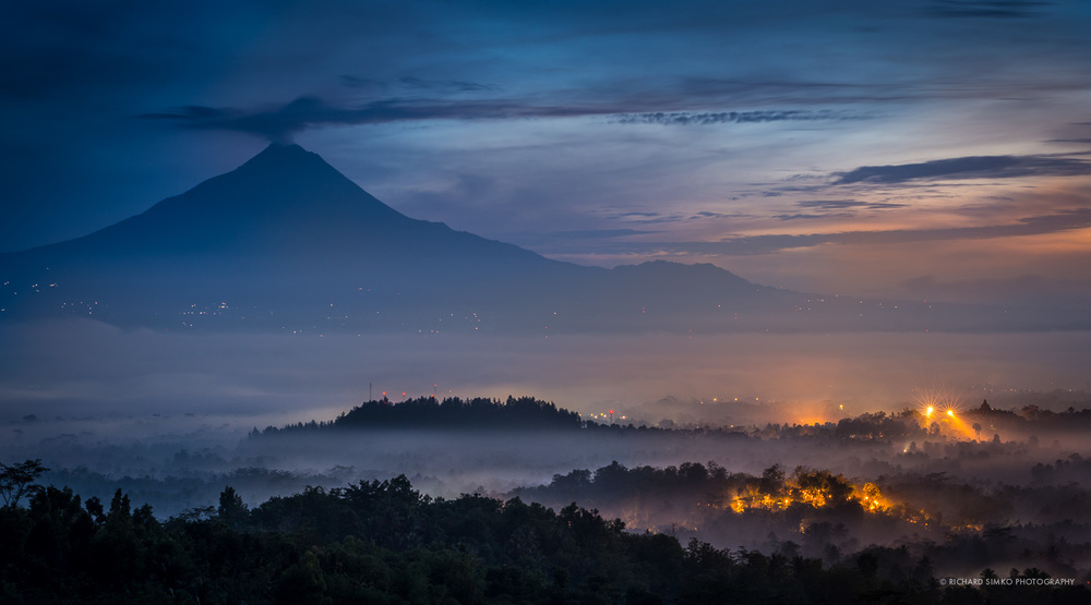 Dawn at Borobudur around 4:30 am. Light at the temple are still on. Merapi volcano is puffing some steam in the background.