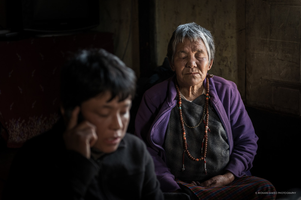 Two generations, mother and daughter are captured on this image from inside traditional Bhutanese house. Although Bhutan has opened to the world recently and spoils of modern technology are just starting to flow it, it is not uncommon to see people with mobile phones even in remote villages. Here the younger woman is making a phone call while the older is quietly mumbling prayer chants. Shot was taken at ISO 6400 at 2.8 thus focus is only on one of the women.