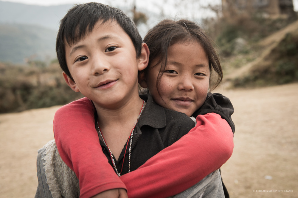 This image is also from Bhutan. We overnight near one of the small villages scattered on the hill side. All of the kids were naturally curious about big white stranger who came to visit their village. They were very nice and playful, genuinely interested in conversation and especially my camera.  This brief moment lasted only second or two when this young girl leaned and hugged the boy in front of her. To me it feels like act of friendship or love with the innocent child feel to it.