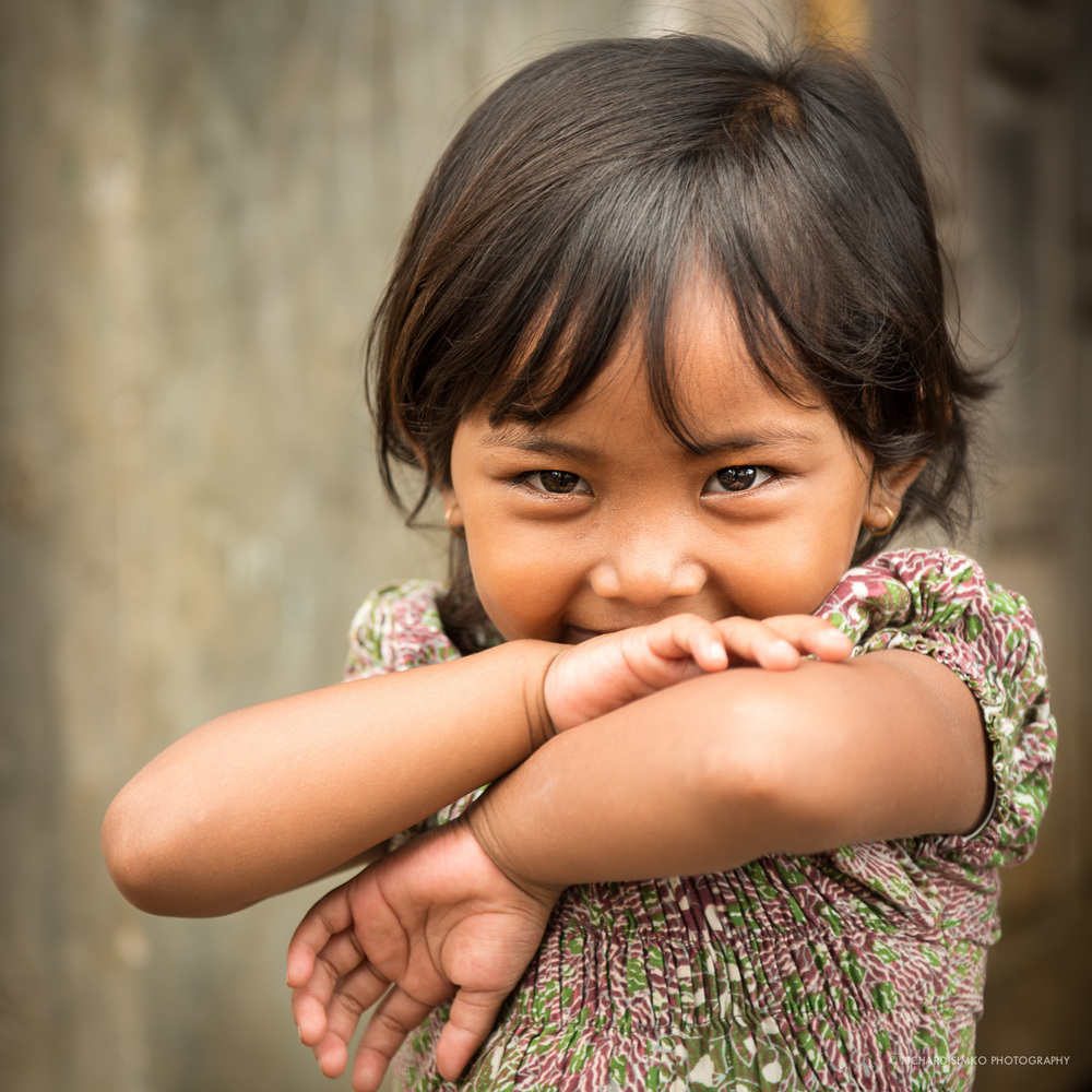 I was probably the first white person this little Javanese girl saw in real life. The village I took this photo in was not visited by tourist before. All people were very kind and children especially very curious. I can see in her eyes the struggle between curiosity and shyness. I asked her mother for permition to take the photograph. When I lifted the camera she became more shy I guess but I think it adds to the picture rather than takes from it.