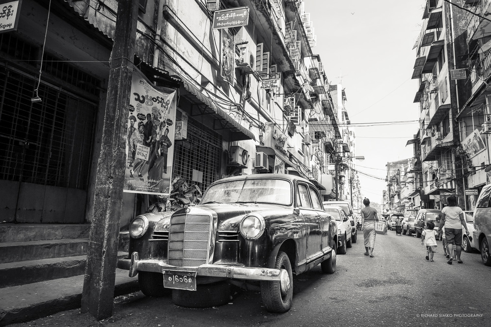 Yangon is the biggest city in Burma. it offers countless opportunities for photography with it's narrow picturesque streets and kind local population. One can often find himself traveling back in time and see things that are fairly uncommon in modern western society. Well preserved mercedes like this one is worth a fortune to enthusiast and car collectors. Yet it stands on this street untouched probably for several years.