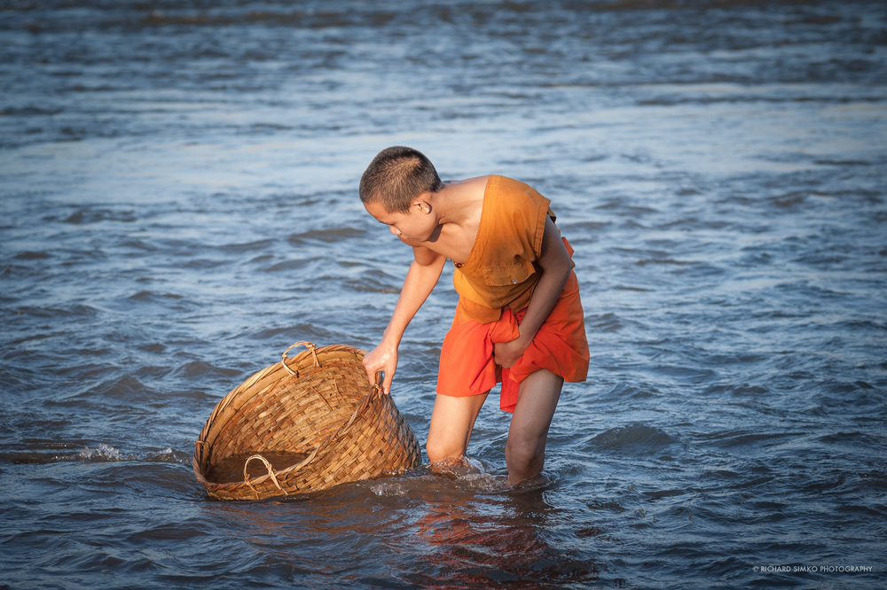 Mekong river means life to people and communities that live along it's banks. It provides food, means of transportation, sometimes home or simply source of water for watering garden. I befriended this young monk.He is helping his grandmother to pump some water into the garden by placing a water pump in the basket to the river.. Later he connects a long hose pipe to the pump and voila. garden is going to get some water.