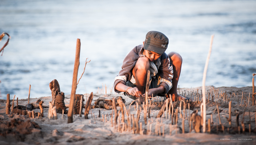 There is a sandy beach at confluence of Mekong and Na,m Khan rivers in Luang Prabang. Perfect place for kids to play. And everything that can be found on the beach can be turned into a toy. This little boy has build a fortress from wooden sticks and branches.