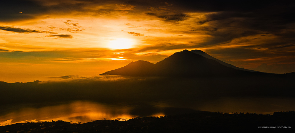 Indonesia lies on Pacific Ring of Fire and entire country has more than 100 sleeping or active volcanoes. Land around these giants is fertile and it is reason for local population to stay there in spite of looming danger of eruption. Some of these volcanoes are very popular tourist destinations. This photograph is taken from Batur volcano in Bali overlooking across the lake to it's bigger brother Mt Angung..