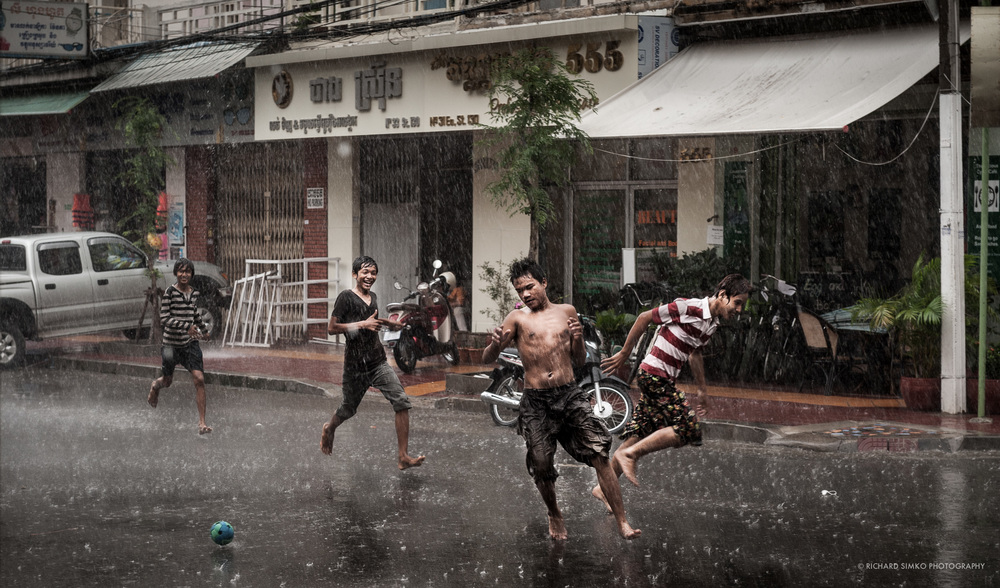 In Phnom Penh streets often serve as playground. If it happens to rain, it is even better. Whole street is available for a game of soccer. These boys evidently enjoy the game and downpour doesn't bother them at all. This is how life supposed to be....happy.