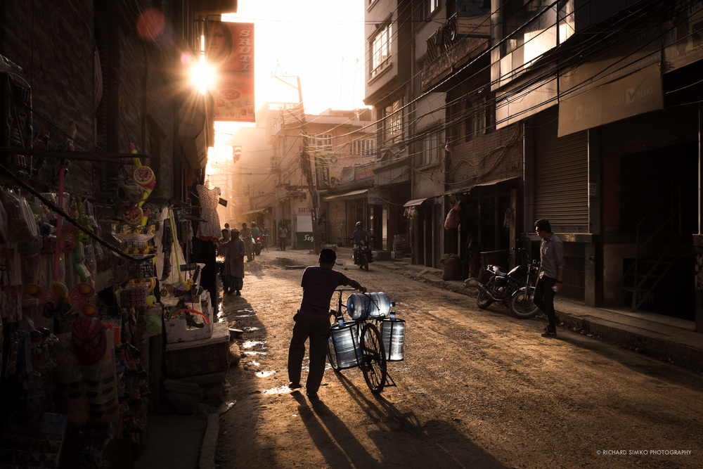 """Sunset at dusty Thamel streets. I picked the image because of the color.. It is almost entirely monochrome except the bluish water drums mounted on the bicycle. I like how they stand out in the sea of yellow/reddish color of environment. I returned back to this place few months later but road on this street has tarmac on it now and it lost a little of it's """"dusty"""" magic."""
