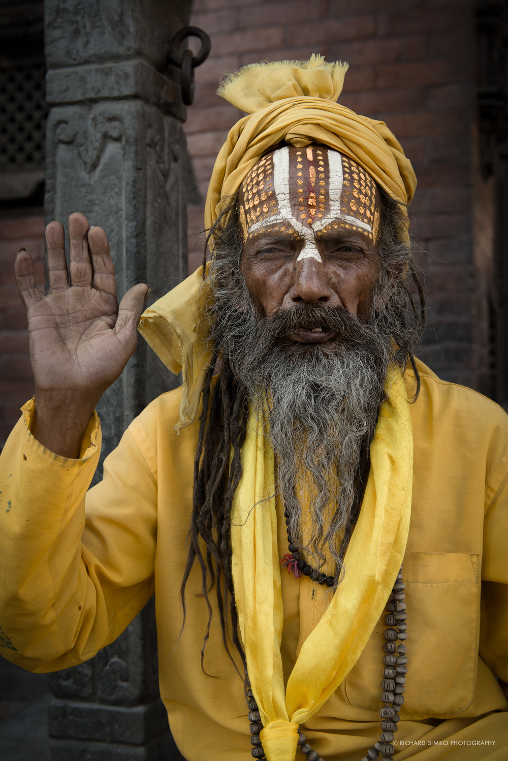 "Sadhu. These characters can be seen on or near Durbar Square. Be careful, there are some that only dress up this way to lure some money from tourists wanting to photograph them. You can recognise them as they literally follow people and their clothing and face paint are quite clean. This guy was just sitting there, not particularly clean. He seemed to be genuine (I might be wrong) compared to the other guy who followed me for few minutes demanding to take photo of him for money. This would be a standard, i would say ""Steve McCurryish"" style of travel portrait. There is not too much special about it but I still like the pose, the colors the character."