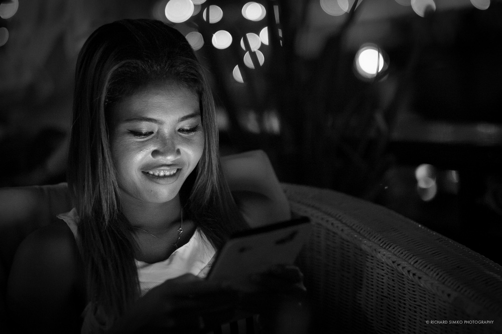 Photograph of my friend Lina in Cambodia. We were sitting in boat restaurant with my friends enjoying a dinner. It was quite dark to photograph anything even with lens wide open. As it happens a mobile phone is a common companion even on social events. It can be bad but in this case it was so much needed light source.. I thing the resulting photograph is not too shabby for ISO 6400. What do you think?