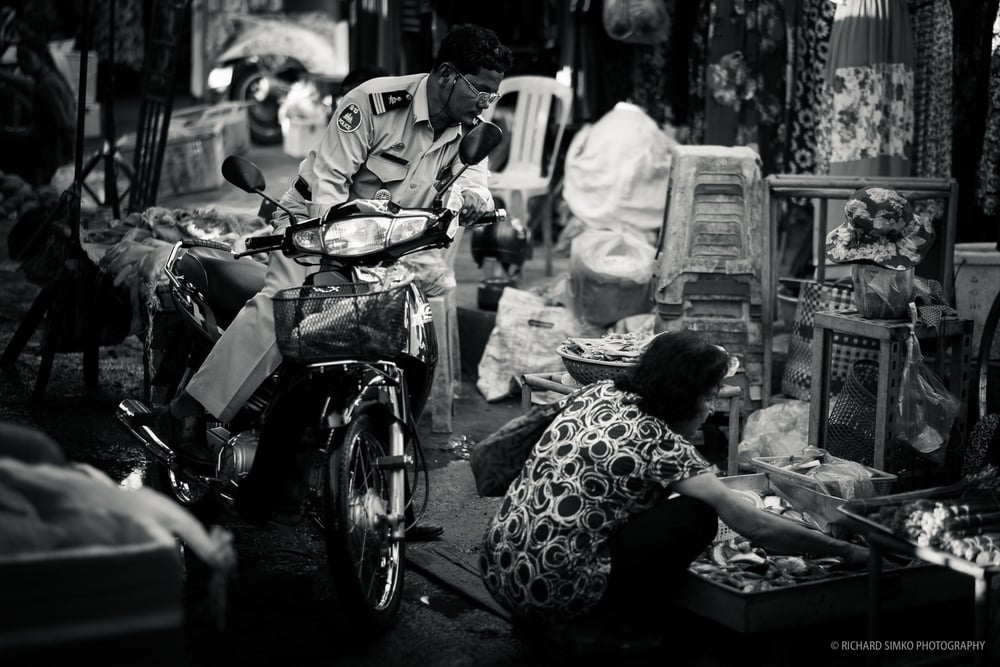 This is a typical scene from any South_East Asian market. Narrow pathways, just wide enough to move through. This doesn't stop people on motorbikes to go in and do their shopping without getting of the bike. This particular photograph was taken in Kandal market in Phnom Penh.