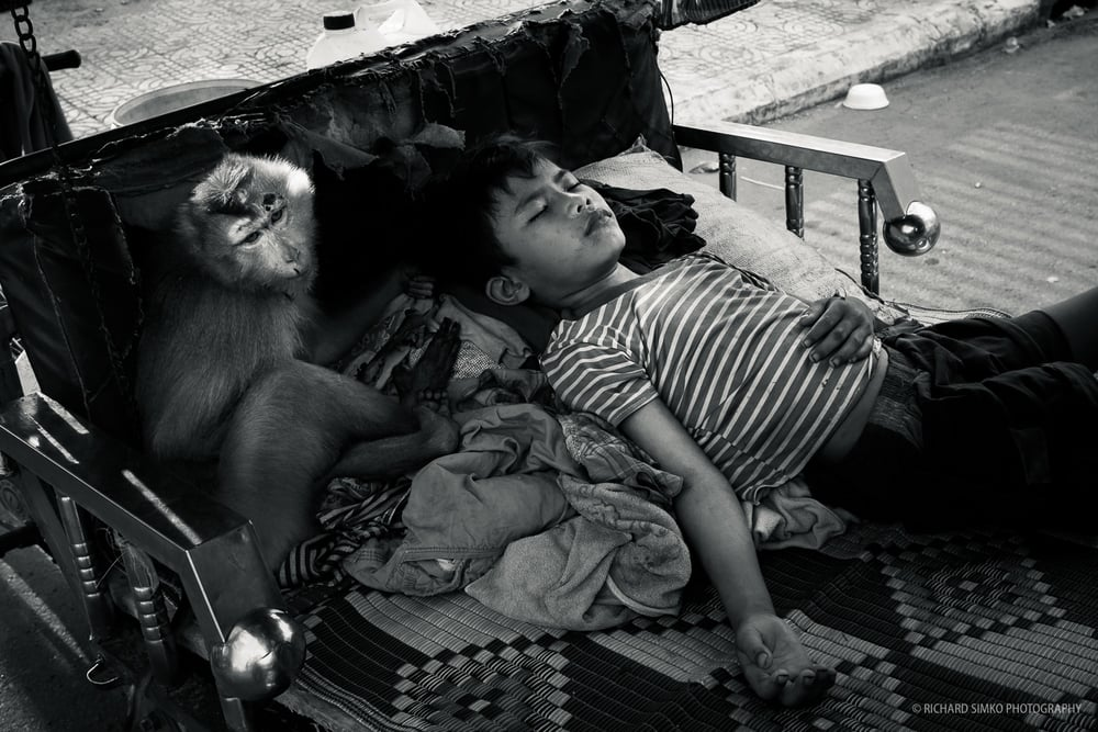 This is a scene I came across during my walks on the streets of very hot Phnom Penh day. Little boy is taking nap in the shade of tuk-tuk roof while his little monkey pet is sitting by his side like guardian angel. My feelings from this photograph can be described by single word. Peace.
