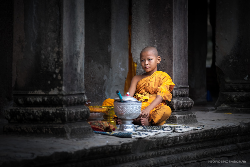 Young monk relaxing inside Angkor Wat temple.  Fujifilm X-T1, Fujinon 50-140mm   2.8