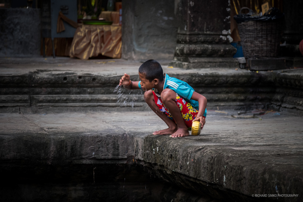 A boy is washing his face inside Angkor Wat temple.  Fujifilm X-T1, Fujinon 50-140mm   2.8