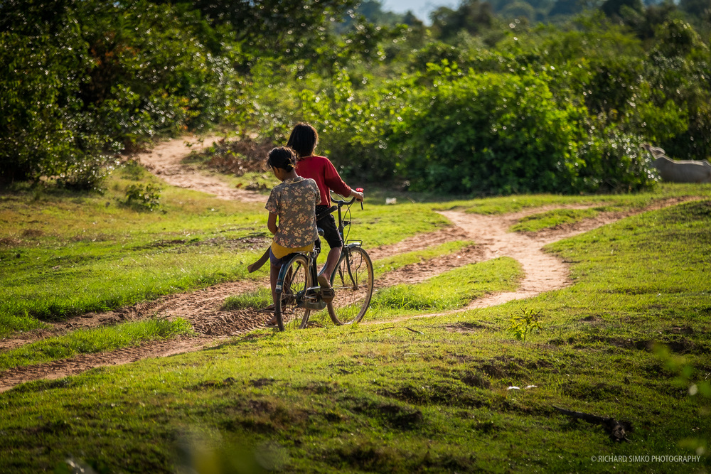 Young girls riding the bicycle in the fields, somewhere near Siem Reap.  Fujifilm X-T1, Fujinon 50-140mm   2.8