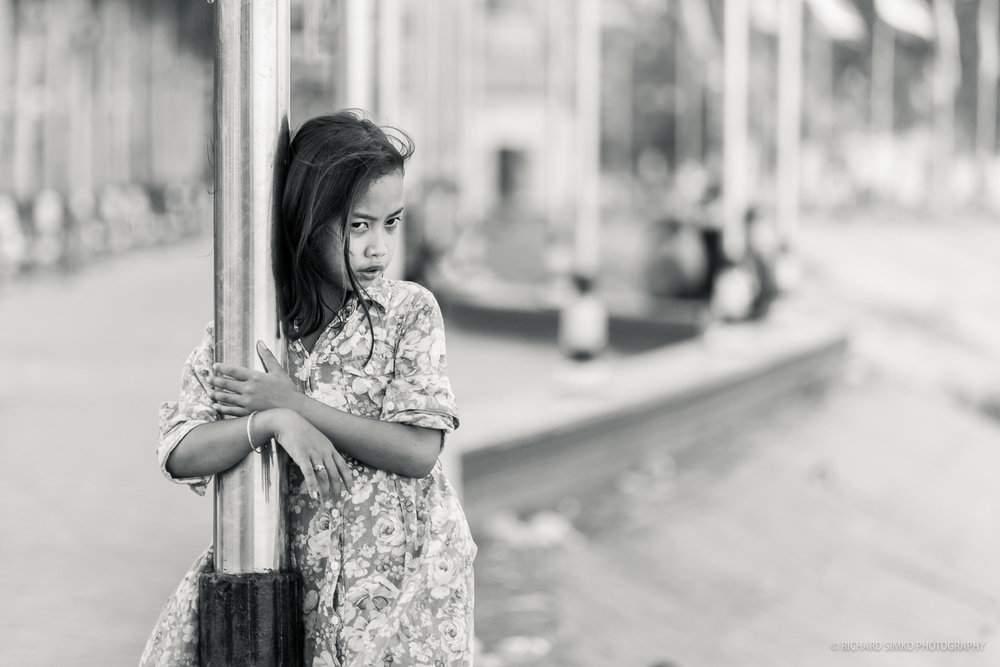I love Phnom Penh's riverside. Life is happening right there. It is a popular area for tourists and locals alike. They are gathering in big numbers during weekends and public holidays. I often just walk up and down and observing life. Time to time I come across a captivating scene. Like this young Cambodian girl hugging the flag pole and having this dreamy stare into distance. I quickly focused and exposed the photograph the very moment she glanced at me.
