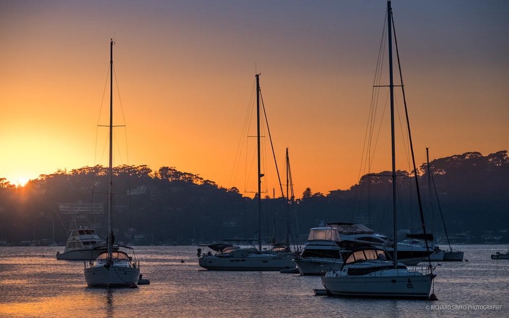 The sunrise glow above the Pittwater bay.