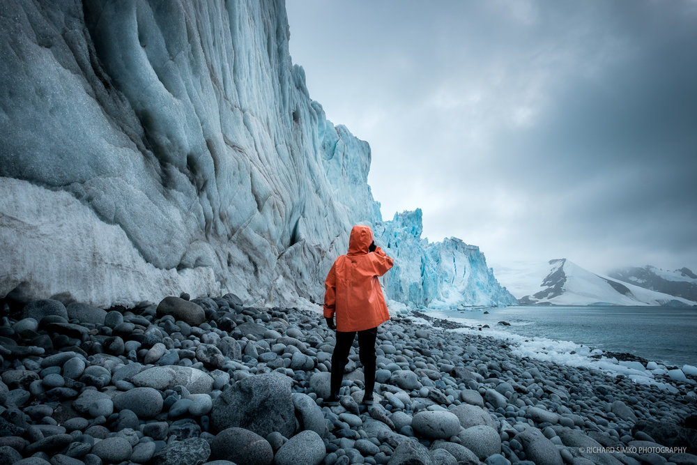 """I rarely wear bright colored clothing. In case of photographing people in Antarctic landscape, the bright colors are a must. I had to gram Julie, one half of the """"team orange"""" (hi Carlos) and positioned her next to the huge terminus of a glacier. The orange jacket stands out nicely against the teal/blueish background. Perfect."""