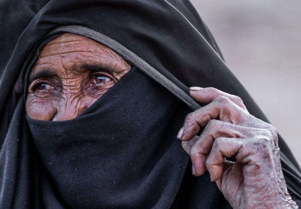 """It is very hard to take a good photo of any Bedouin female. There are cultural and religious customs that need to be respected and I as a male I am not allowed to take a photo of females in most cases. Here and there you came across one that doesn't mind and this was the case. A very nice older lady agreed to be photographed. I was not in the best position for this shot as there were few people in front of me but I snapped a general good shot and then I found this """"picture in picture"""". It is a heavy crop, but for online publishing, it works."""