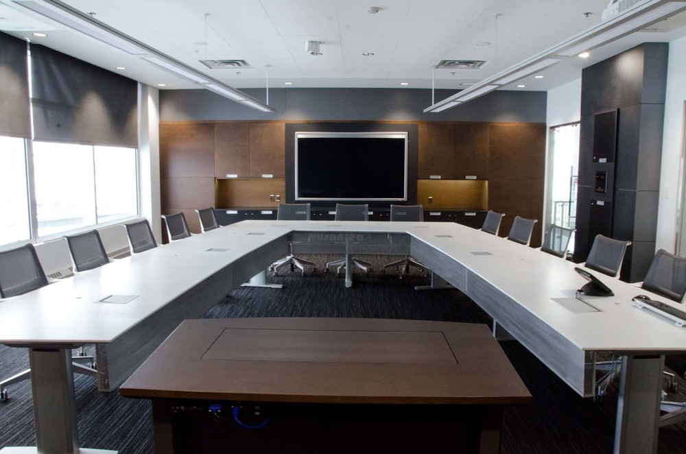 Presentations can be made at either end of conference room. All AV equipment is contained and controlled in mill-work at side of room. Lighting is on 6 separate zones and is programmed in scenes for each type of presentation. Controls by Crestron. Custom Conference table by Nienkamper. Chairs by Herman Miller. Millwork by Twin Creek Woodcraft