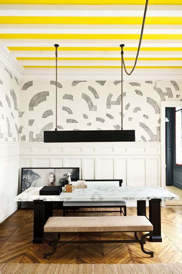 The original cove ceiling in this space was highlighted by painting the area between the beams lemon yellow. The brilliant colour beautifully balances all the rich textures in the room.