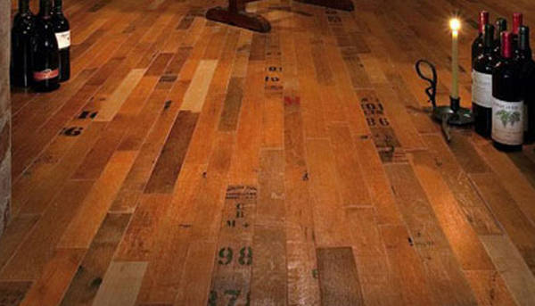 This  wood flooring is made from old oak wine barrels by Blue Grouse Wine Cellars. The staves of the old barrels are pulled away from the hoops and peeled into wood veneers which are laminated to engineered baltic birch flooring. The flooring is available in three different formats: cooperage (shown in this illustration), which comes from the outside of the barrel heads showing the cooperage stamps; wine infusion, which comes from the inside of the barrel heads showing the red wine stain; and staves, which come from the body of the barrel showing the markings of the hoops.