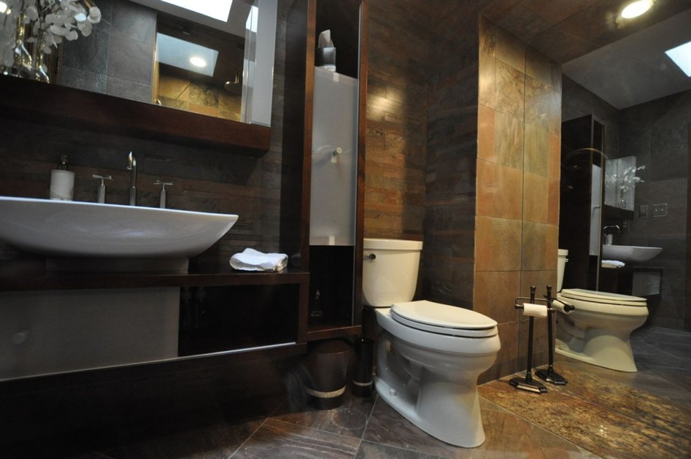 This powder room makes use of a full height mirror on the end wall and a skylight to visually expand the space. A full height wall cabinet has a glass door that slides up and down to allow some open display and some closed storage.Sliding glass doors below the sink also allow full access to this cabinet. Partially recessed mirror cabinet above sink with a built in light bar each side provides the best lighting for make-up or shaving...no awful downward shadows!!!.