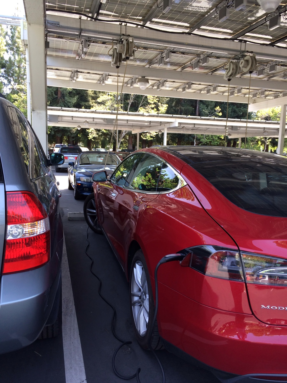 A Tesla Model S charging under the Google solar canopy. Not one but TWO Tesla Roadsters were parked on the other side.