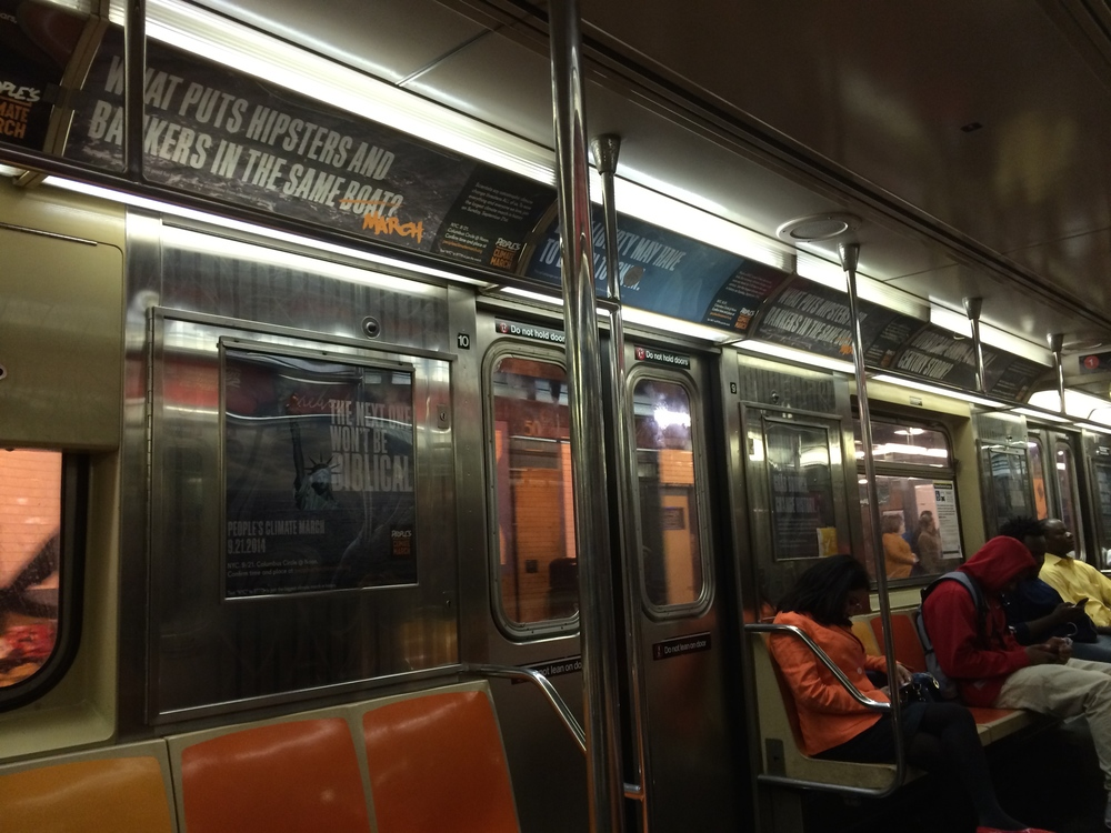 NYC Subway car, covered in signs encouraging people to attend the march