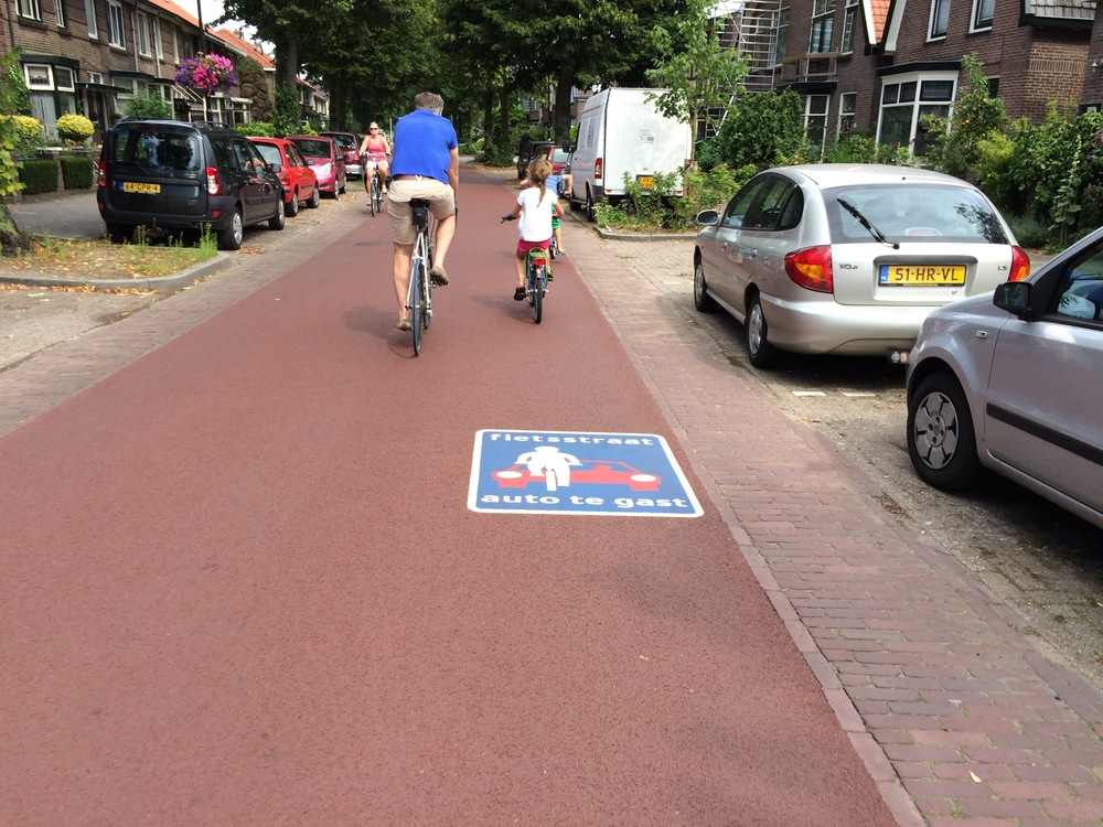 "Deventer ""bike street"". Sign reads ""autos are guests""."