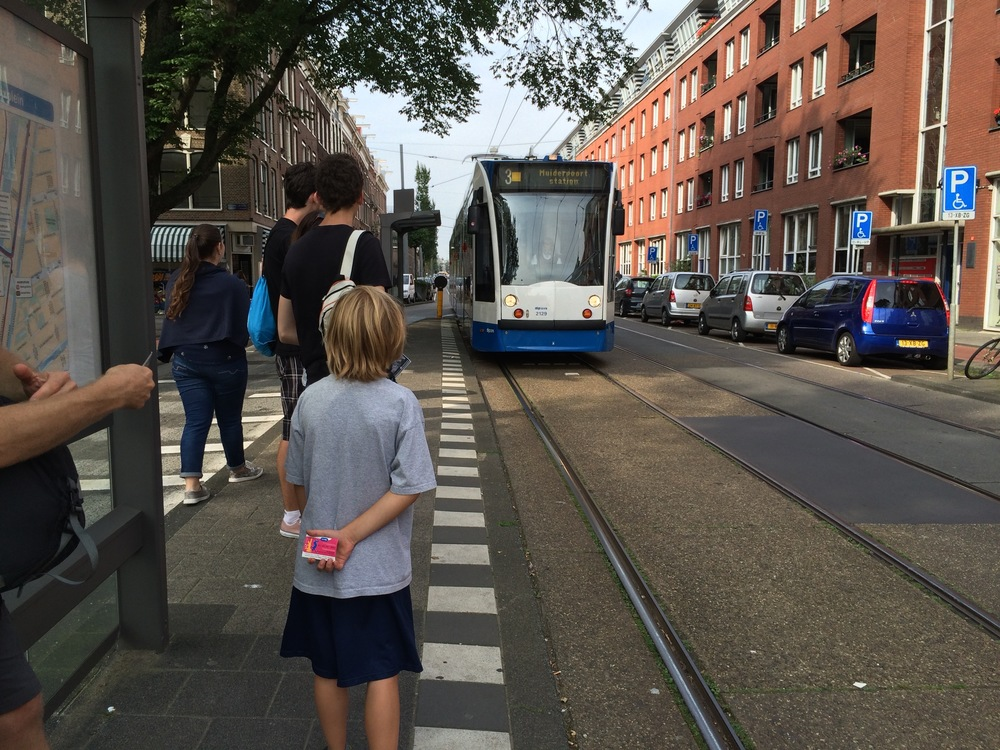 Elliot waits for a tram in Amsterdam