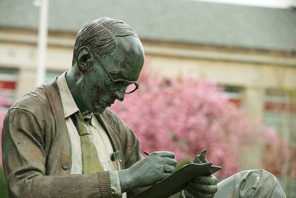 Hofstra University's Walter statue poses in front of Calkins Hall and a blooming cherry blossom tree.