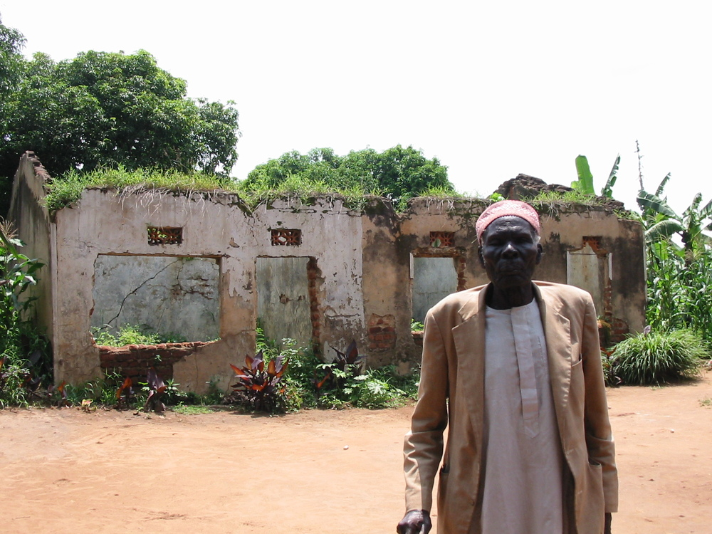 The skeletal remains of Mohammed Anyule's house in Yumbe (a relative stands in the foreground) (Andrew Rice)