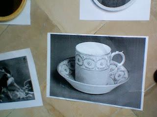 Een zwart-wit foto van een kopje (uit zaal 10) op de vloer.