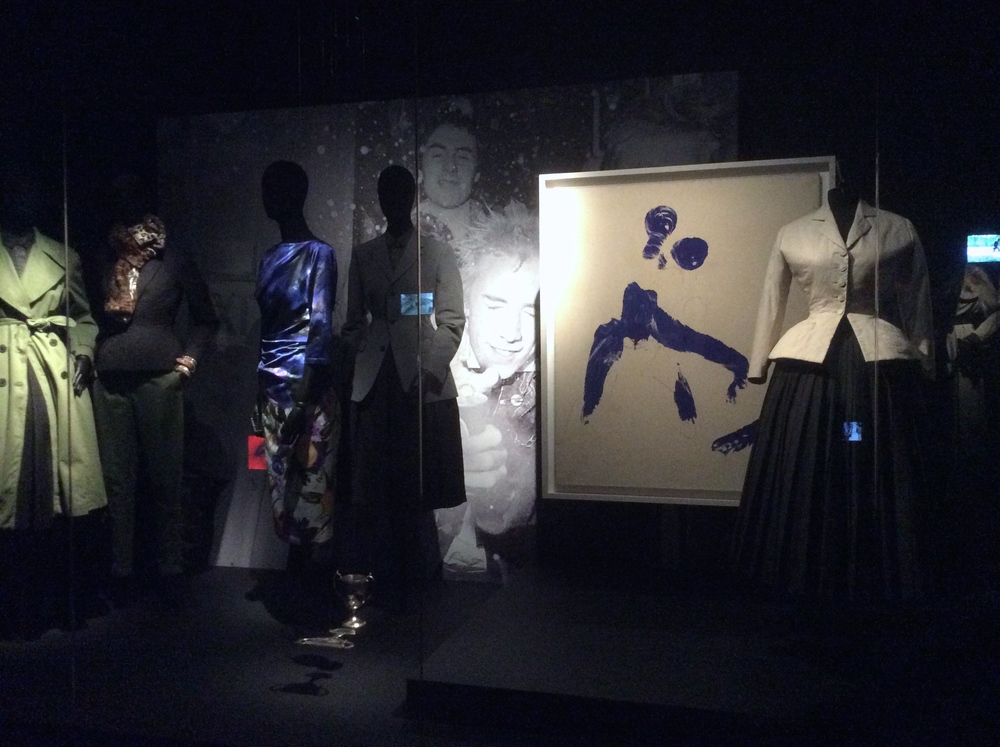 v.l.n.r.: collectiestukken Dries Van Noten (2010), foto van de Sex Pistols, Monique ant 57van Yves Klein (1960) en een replica naar de Bar tailleur van Christian Dior uit 1947. Ook is in deze vitrine een verwijzing naar Alfred Hitchcocks Vertigo(1958) te zien.