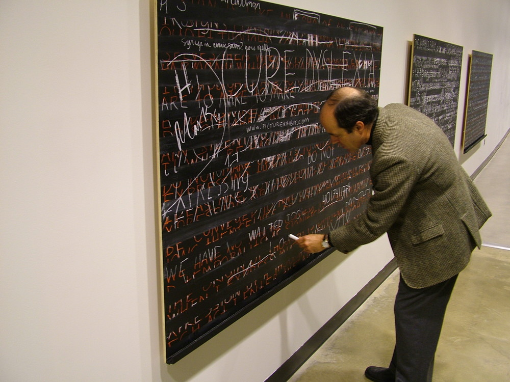 """Logocentric Playground: A Sign ; 2006; blackboard paint; chalk, pastel, pencil on birch panel; H48""""xW69"""" (Museum visitor interacts with installation.)"""