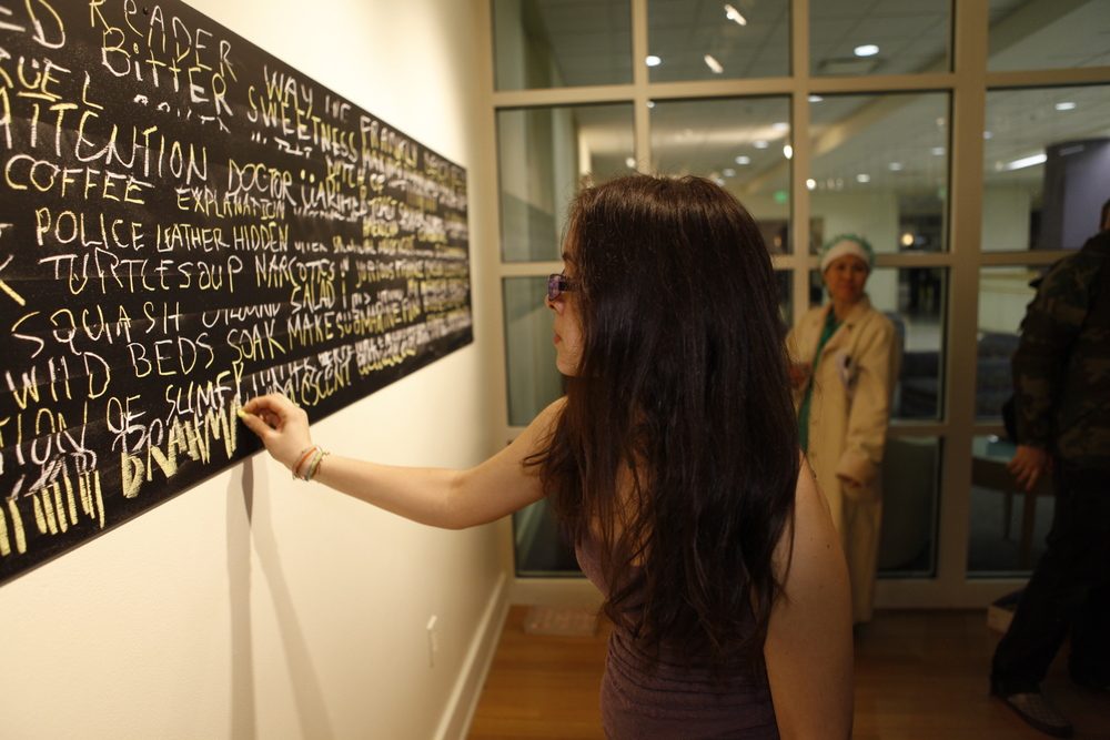 """Gallery visitor interacts with     Welcome, reader!     during opening reception for """" Postconceptualism: The Malleable Object""""  that Boyd curated for University of Maryland's Stamp Gallery; 2011."""