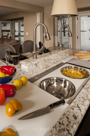 Kitchen design featuring Galley Sink with stainless bowl and colander.