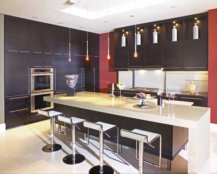 Contemporary kitchen design with a kitchen island featuring dark cabinetry and a white waterfall countertop.