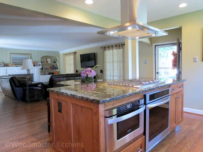 Kitchen design with a ceiling mounted island hood in stainless steel.
