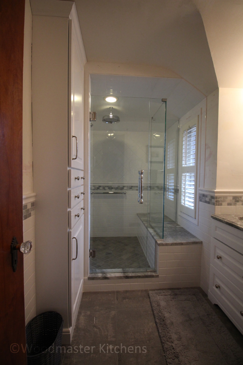 Bathroom design featuring a large shower with a built-in ledge.