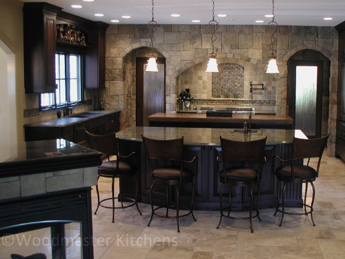 Kitchen design with a recessed range with stone surround, stone tiles, and mosaic tile detail.