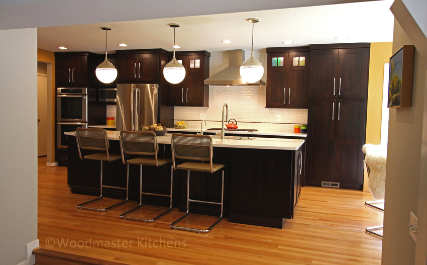 Kitchen design showing after photos with dark wood cabinetry.
