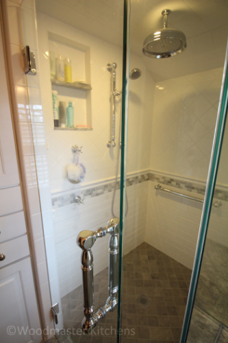 Built in storage shelves in a shower in this bathroom design.