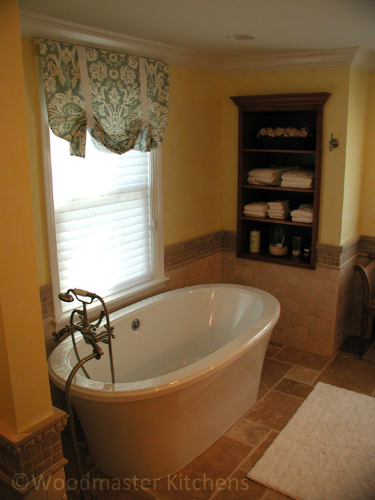 Built in storage shelves near a freestanding tub in this bathroom design.