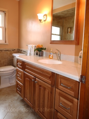 Traditional bathroom design with vanity in warm wood tones.