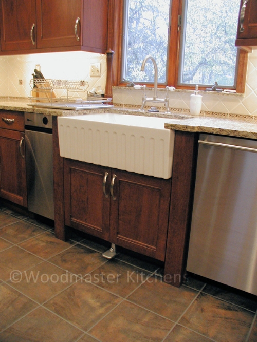 Kitchen design featuring a farmhouse sink with a foot pedal controlled faucet.