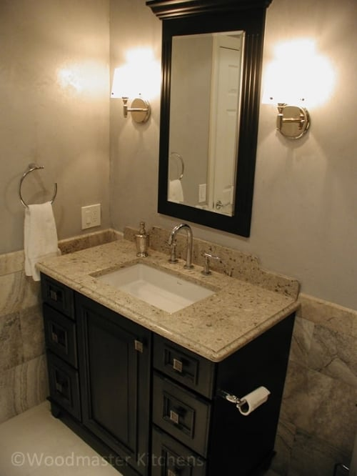 Bathroom design with a dark wood framed mirror to match the vanity.
