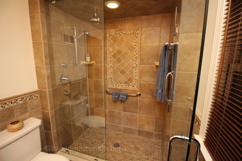 Bathroom design with large shower with a tile feature and grab bars.