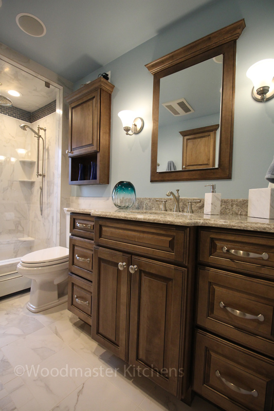 Bathroom design with partially recessed toilet topper cabinet