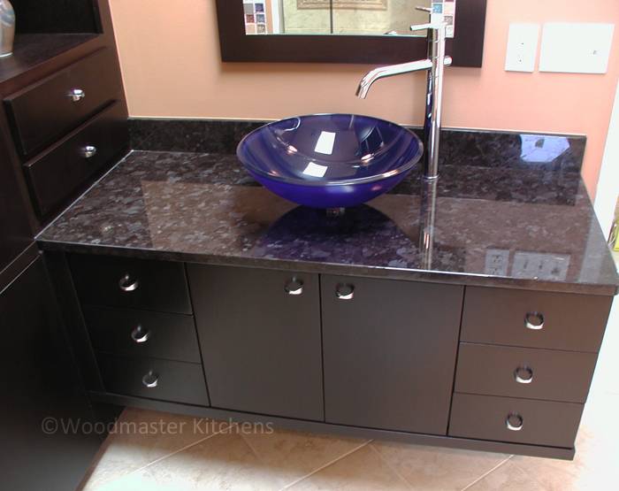 Blue glass vessel sink on a dark vanity and countertop.